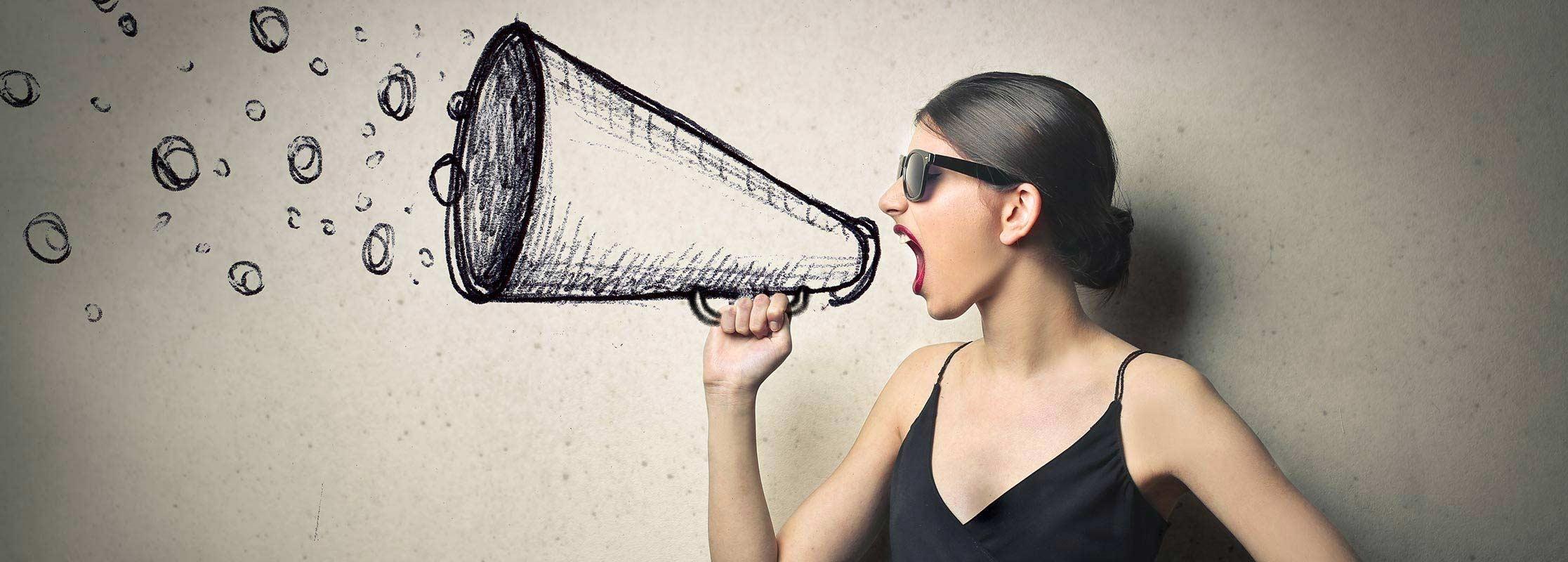 Junge Frau schreit in ein Megafon, Marketing studieren an der TRIAGON Akademie